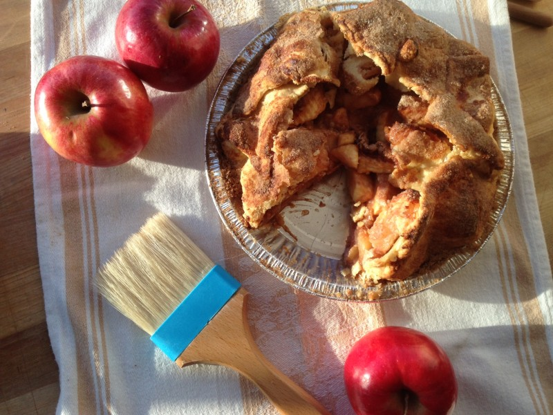 Apple pie with a slice cut out and apples around it